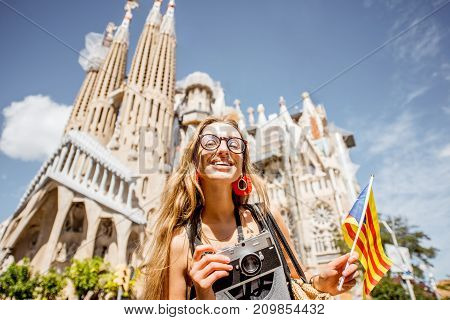 BARCELONA, SPAIN - August 16, 2017: Young woman tourist standing with catalan flag in front of the famous Sagrada Familia Roman Catholic church in Barcelona, designed by architect Antoni Gaudi