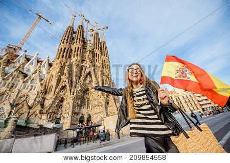 BARCELONA, SPAIN - August 17, 2017: Young woman with spanish flag in front of the famous Sagrada Familia roman catholic church in Barcelona, designed by catalan architect Antoni Gaudi