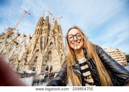 BARCELONA, SPAIN - August 17, 2017: Young woman taking selfie photo in front of the famous Sagrada Familia roman catholic church in Barcelona, designed by catalan architect Antoni Gaudi