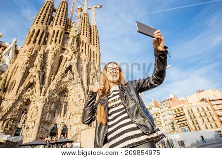BARCELONA, SPAIN - August 17, 2017: Young woman photographing in front of the famous Sagrada Familia roman catholic church in Barcelona, designed by catalan architect Antoni Gaudi