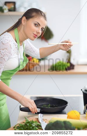 Young woman housewife cooking in the kitchen. Concept of fresh and healthy meal at home.
