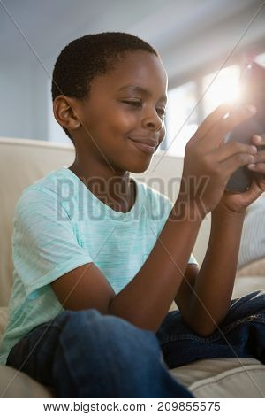 Boy using mobile phone in the living room at home