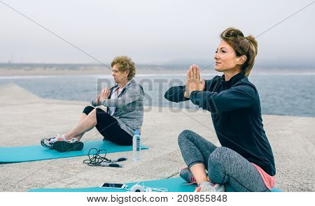 Young and senior woman doing exercise sitting outdoors by sea pier