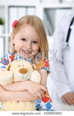 Doctor and patient in hospital. Child being examined by physician with stethoscope.