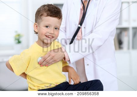 Doctor and patient in hospital. Happy little boy having fun while being examined with stethoscope. Healthcare and insurance concept.