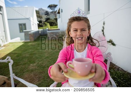 Portrait of girl in fairy costume holding coffee cup