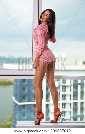Beautiful smiling woman with perfect legs posing near the window in red striped shirt and high heels. Beauty fashion portrait.