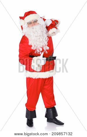 Santa Claus carrying big bag and showing thumbs up or ok isolated on white background. Full length portrait.
