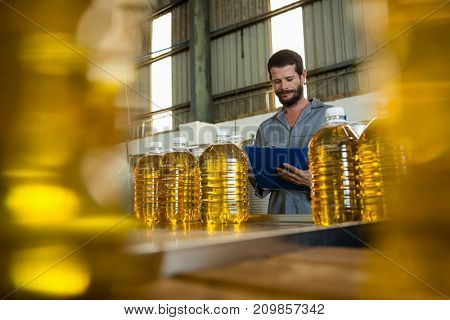 Attentive worker writing on clipboard in olive factory