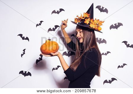 a young sexy gothic girl in the shape of a witch in halloween, in a big black hat, adorned with yellow leaves, holds a pumpkin and a knife in her hand