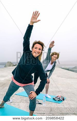Happy personal trainer with senior woman stretching side by sea pier