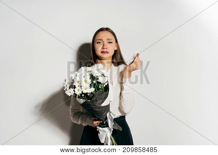 a young girl holds a bouquet of white flowers, but sneezes because she has an allergy