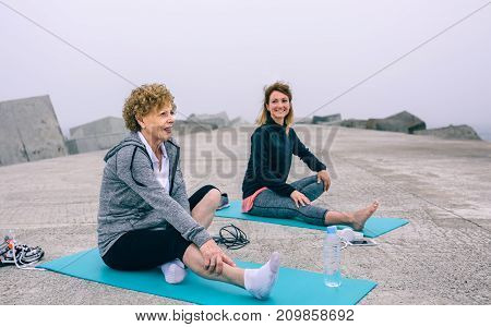 Senior woman stretching legs with female coach by sea pier