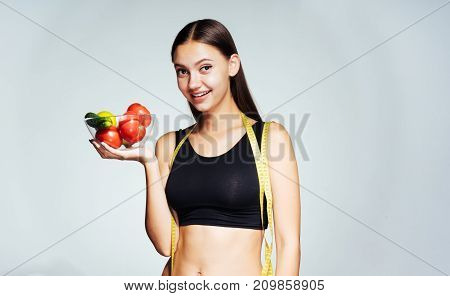 young beautiful sporty girl follows her figure, holds a plate with useful vegetables and fruits