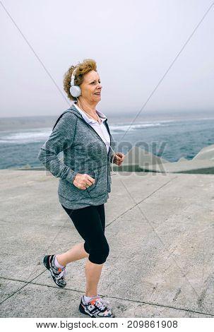 Senior sportswoman listening music with headphones while running