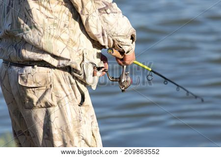 fisherman with a fishing rod on the river .