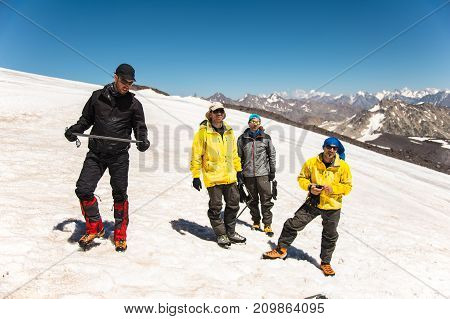 Training to correct slip on a slope or a glacier with the help of an ice ax. A young guide with a beard explains to his group how to properly slow the slip on the slope with the help of an ice ax. Preparation before climbing to the top of the mountain