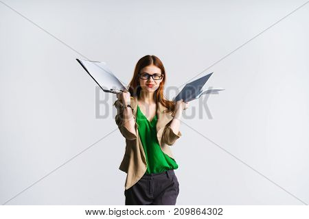 the girl is at work. red-haired lady with glasses holds a folder of documents in her hands and looks at the camera