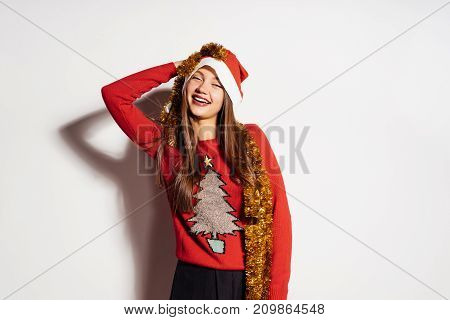 a young girl looks happy, celebrates a new year and Christmas in a red cap and gold tinsel