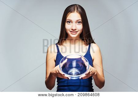 young beautiful sporty girl watching her figure holding an empty glass plate