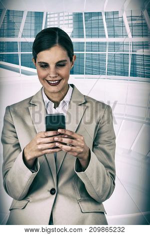 Beautiful businesswoman using mobile phone against modern room overlooking city