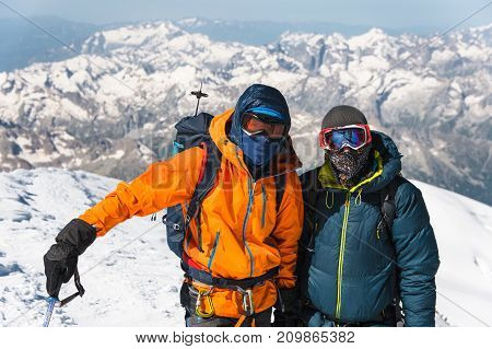 Portrait A middle-aged climber in a down jacket he is standing next to his friend on the way to the top of a snow-capped mountain. The concept of rest and climbing high mountains with friends