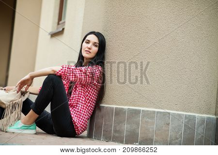 cute young girl sitting on ground near building, pretty woman in pink jacket and black pants with bag relaxing outdoor