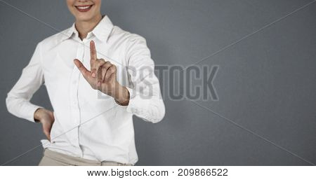 Mid section of smiling businesswoman using invisible screen against grey background