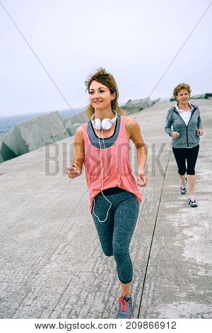 Young and senior sportswoman running by sea pier
