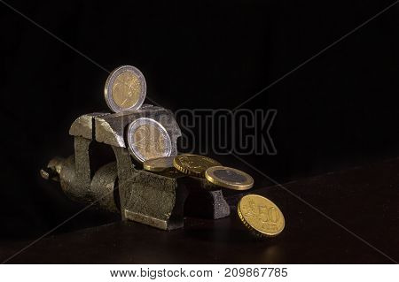 Coins clamped in a jaw vice on dark background