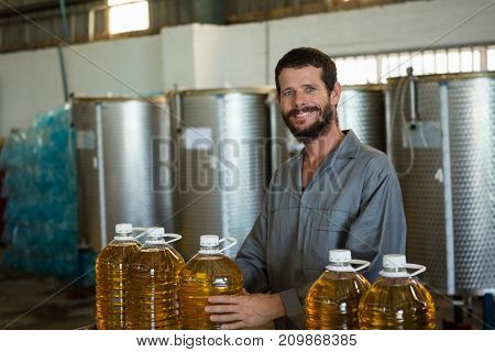 Portrait of smiling worker holding a can of olive oil in factory