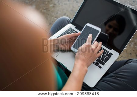 Close-up of female executive using laptop and mobile phone in office