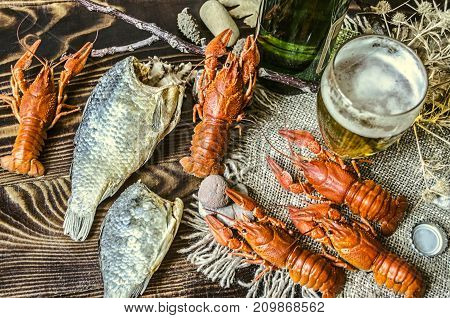 Beer in a glass and a bottle of beer with a snack of boiled crawfish and dried salted fish on dark wood boards