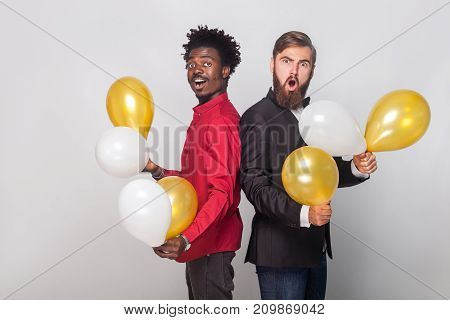 Two Shocked Friend Wearing Red Shirt And Black Jacket Holding Many Air Balloon And Looking At Camera