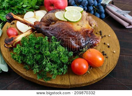 Baked goose legs served with apples vegetables grapes greens on a round oak tray on a dark wooden table.