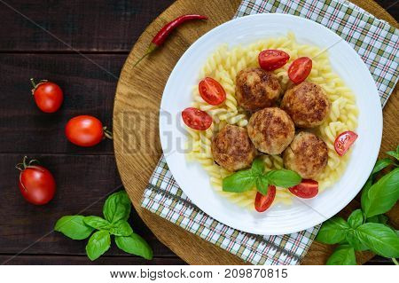 Chicken meat balls pasta fusilli tomatoes basil on a white plate on a wooden tray. Top view.