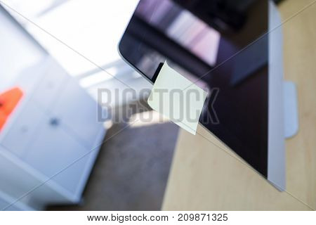 Close-up of blank sticky note over computer monitor in office