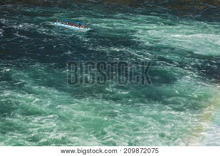 Laufen, Switzerland - 17 October, 2017: a boat on the Rhine river just below the Rhine Falls view from the Laufen castle. The Rhine Falls is the largest waterfall in Europe located on the border between the Swiss cantons of Zurich and Schaffhausen.