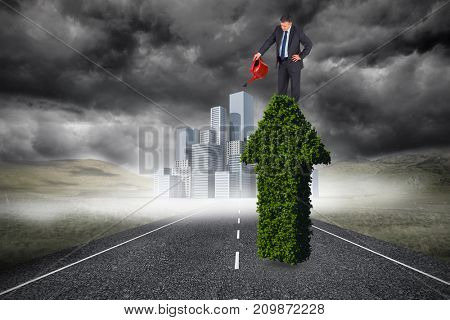 Mature businessman using watering can against cityscape on stormy landscape background