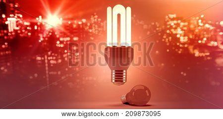 Illuminated buildings in city against sky against composite image of illuminated energy efficient lightbulb over bulb