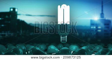 Illuminated buildings in city against sky against digital composite image of lit energy efficient lightbulb over bulbs