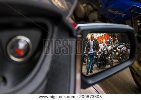 Uzhhorod Ukraine - July 9 2016: Blurred reflection of bikers in the mirror of a motorcycle in a parking in the city center.
