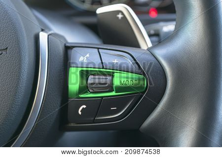 Hands free and media control buttons on the steering wheel in black leather modern car interior details