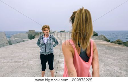 Young woman stretching with senior woman by sea pier