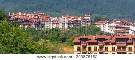 Wooden chalet hotel houses and summer panoramic banner, bulgarian all seasons resort Bansko, Bulgaria
