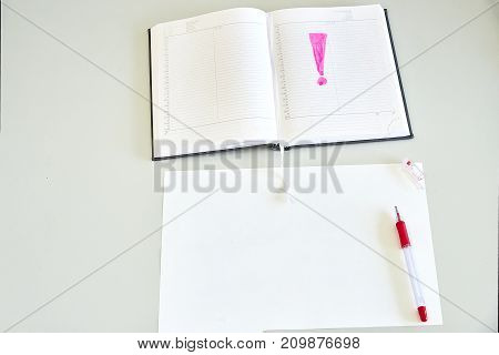 Sheet of paper, diary and red pen on a desk - horizontal