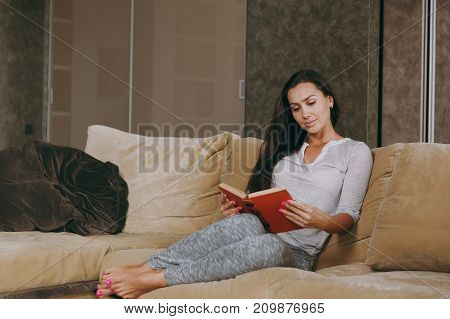 Beautiful Young Woman At Home Sitting On The Sofa, Relaxing In Her Living Room And Reading Book