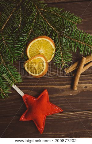 Christmas tree branch with dried oranges and cinnamon on dark wooden background