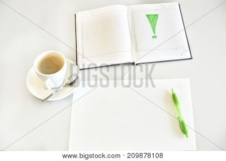 Espresso coffee, sheet of paper, diary and green pen on a desk