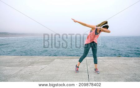 Young woman making dab dance outdoors by sea pier